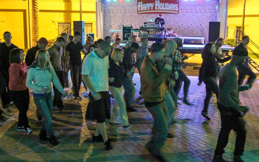Sailors from the aircraft carrier USS Harry S. Truman get their groove on at an open air venue at the U.S. Naval base in Bahrain, where Morale, Welfare and Recreation officials have brought in a DJ to provide entertainment for the arriving crew. The Truman is on a scheduled 5-day port visit to spend Christmas in Bahrain.