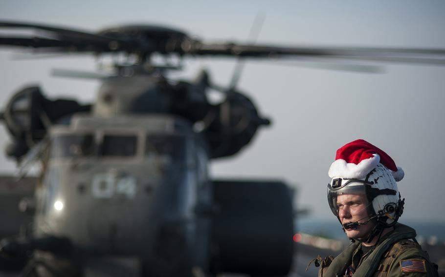 ARABIAN GULF (Dec. 19, 2013) Naval Aircrewman (Helicopter) 3rd Class Tyler Abbott, assigned to the Blackhawks of Helicopter Mine Countermeasures Squadron (HM) 15, waits while mail is unloaded from an MH-53E Sea Dragon helicopter on the flight deck of the aircraft carrier USS Harry S. Truman (CVN 75). Harry S. Truman, flagship for the Harry S. Truman Carrier Strike Group, is deployed to the U.S. 5th Fleet area of responsibility conducting maritime security operations, supporting theater security cooperation efforts and supporting Operation Enduring Freedom. (U.S. Navy photo by Mass Communication Specialist Seaman Karl Anderson/Released)