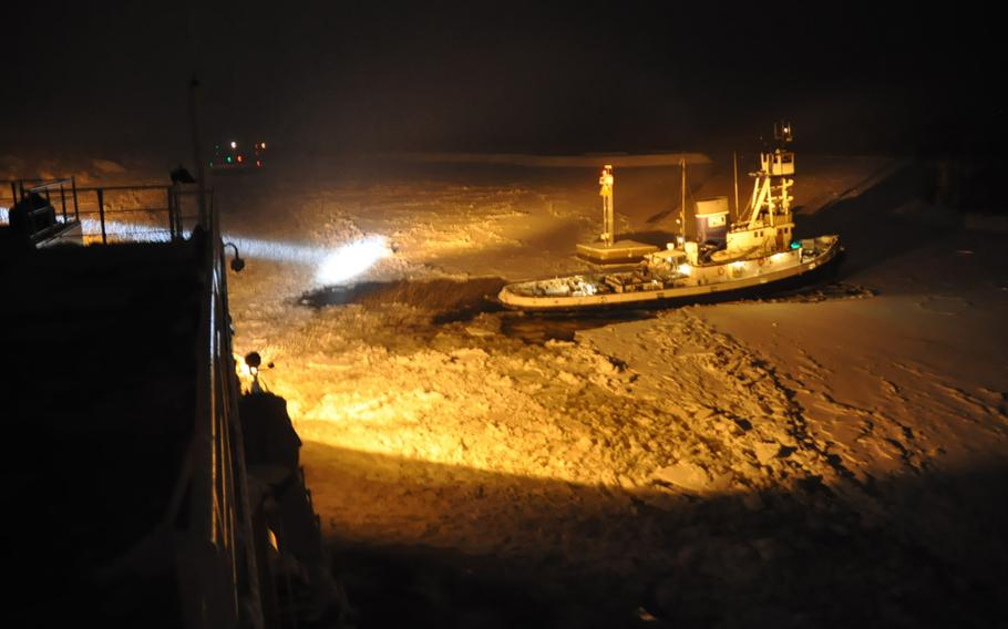 The crew of the Coast Guard Cutter Mackinaw illuminates the ice around the tug Avenger IV as it breaks ice around the tug after it became stuck in the St. Marys River, Dec. 17, 2013.  After the crew of Mackinaw freed the Avenger IV, it freed the vessel the tug was escorting through the St. Marys River.  U.S. Coast Guard photo by Ensign Michael Cooper