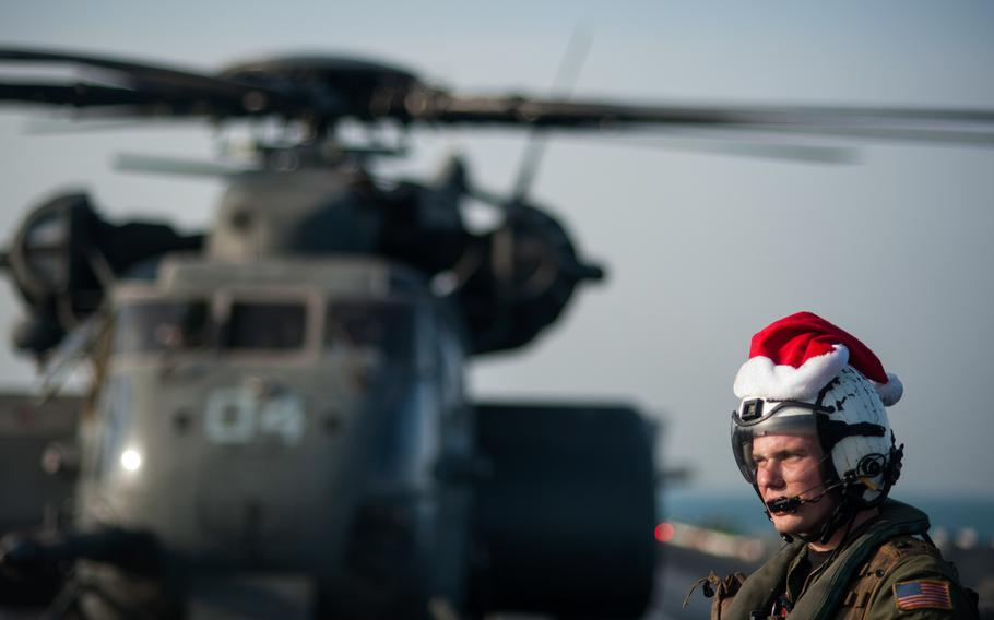 Naval Aircrewman 3rd Class Tyler Abbott, assigned to the Black Hawks of Helicopter Mine Countermeasures Squadron  15, waits while mail is unloaded from an MH-53E Sea Dragon helicopter on the flight deck of the aircraft carrier USS Harry S. Truman Dec. 19, 2013 while underway in the Persian Gulf.