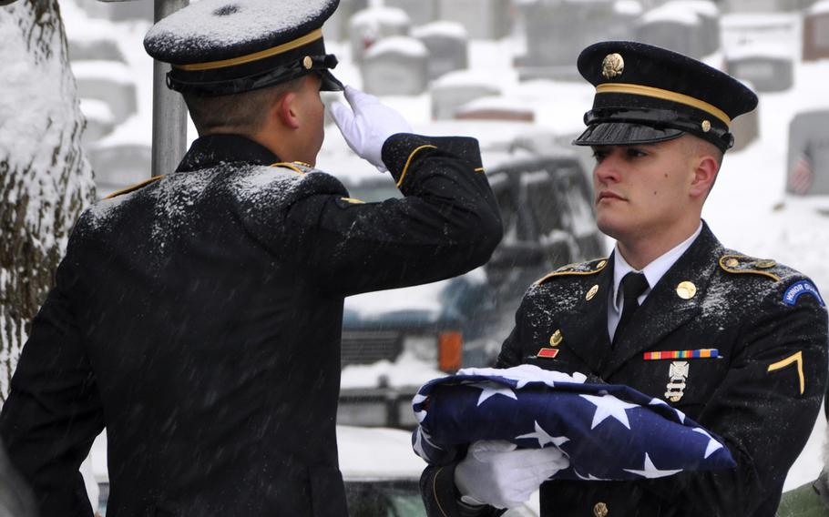 New York Army National Guard Spc. Christopher Roderiguez salutes the flag held by Pvt. Shelbi Vanderbogart as they complete folding the flag to be presented to the family of Army veteran Harold Smith during graveside services in Hudson, N.Y., Dec. 17, 2013.