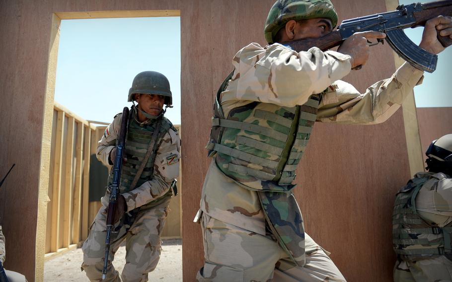 Iraqi army soldiers practice clearing a building during an exercise at Besmaya, a coalition training site south of Baghdad, on April 26, 2015. Coalition advisers say they try to make the exercises as realistic as possible to reflect the threats the Iraqi troops will face in their fight against Islamic State militants.