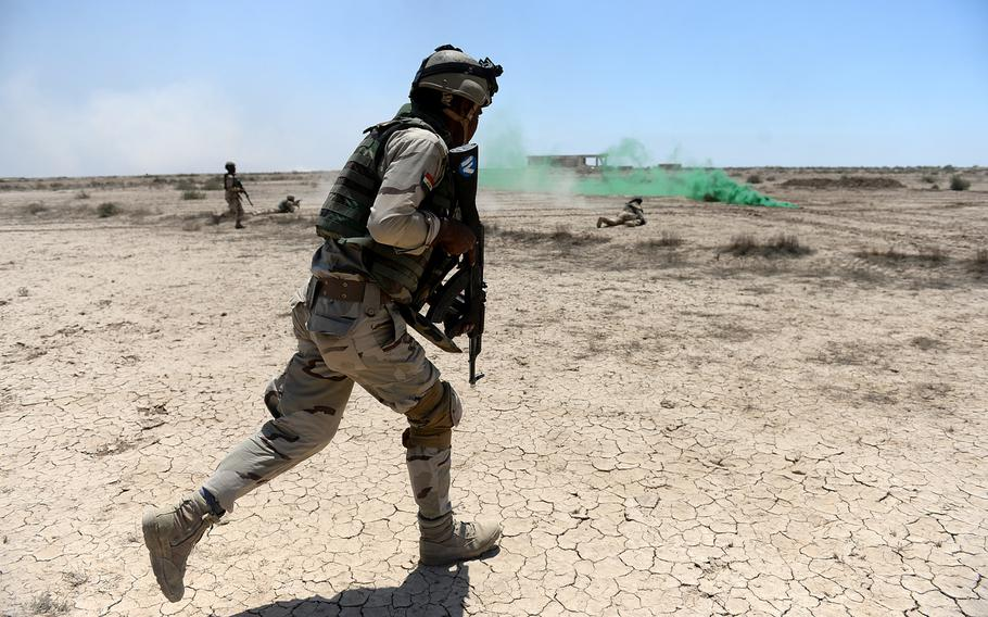 An Iraqi soldier runs across the desert during an exercise at Besmaya, a coalition training site south of Baghdad, on April 26, 2015. The course is designed to give Iraqi soldiers a taste of what they may face when they are deployed to the battlefield.