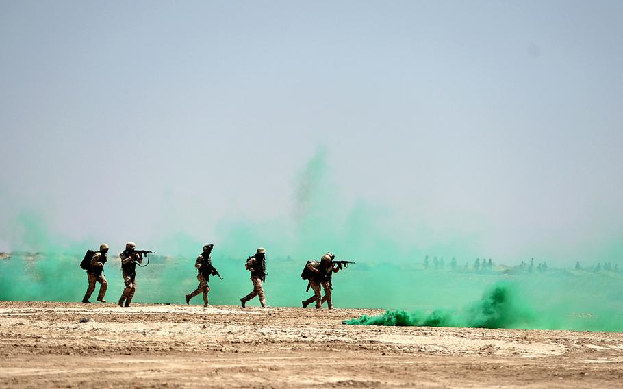Iraqi soldiers run through smoke grenades to take up positions during an exercise at Besmaya, a coalition training site south of Baghdad, on April 26, 2015.