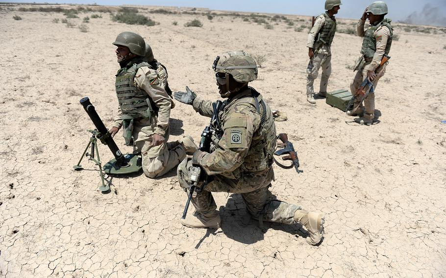 Sgt. Cory Bazemore, a U.S Army adviser in Besmaya, Iraq, instructs an Iraqi army mortar team during an exercise on April 26, 2015. Iraqis come to the coalition-led training with a variety of levels of experience, with some needing more hands on instruction.