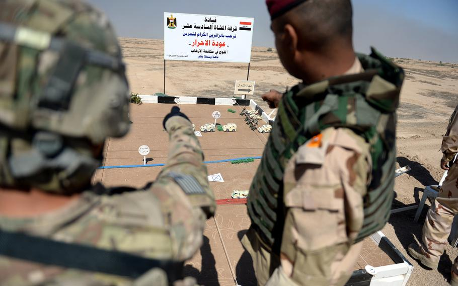 A U.S. soldier, left, and an Iraqi officer use a diorama to plan an exercise for Iraqi troops at the Besmaya training center south of Baghdad.