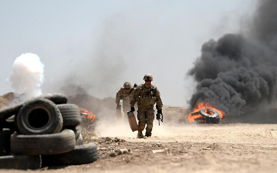 U.S. Army advisers run to safety after lighting tires for realistic effects during an Iraqi army exercise at Besmaya, a coalition training site south of Baghdad on April 26, 2015.