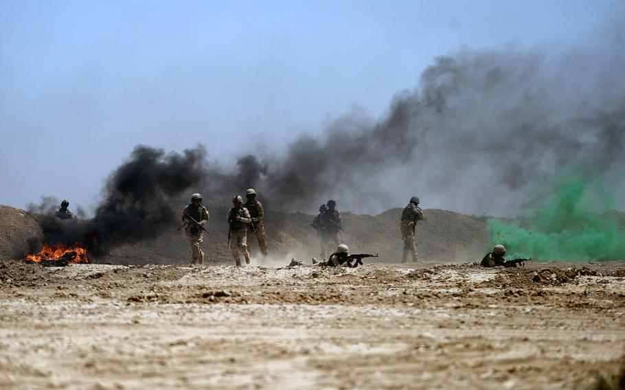 Iraqi army soldiers run through smoke to take up positions during simulated combat at a training exercise on April 26, 2015. Coalition advisers say they try to inject realism into the training as much as possible.