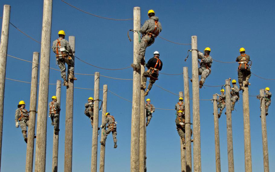 Students of the 364th Training Squadron's electrical systems course practice climbing power poles as part of a familiarization and trust exercise with the safety equipment on Feb. 3, 2015, at Sheppard Air Force Base, Texas.