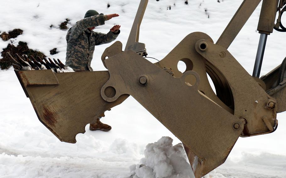 Spc. Isaac Viers, a heavy equipment operator assigned to the Virginia National Guard?s 276th Engineer Battalion directs a high-mobility engineer excavator to remove snow Feb. 28, 2015, throughout communities in Lee County, Va.