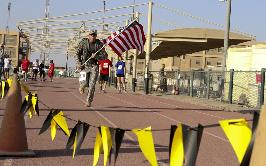Sgt. Christopher Hughes, of the 43rd Sustainment Brigade, 4th Infantry Division, carries the American flag across the finish line at the Army Marathon Shadow Run on March 1, 2015, at Camp Arifjan, Kuwait.