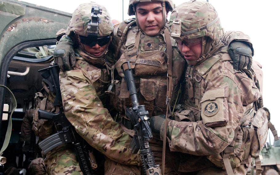 Pvt. D?Angelo Ravizee, left, and Pvt. 1st Class Shane Baer carry Spc. Tobbi Hurtado, a team leader with K Troop, 3rd Squadron, 2nd Cavalry Regiment, to safety during a raid exercise at Drawsko Pomorskie Land Forces Training Center, Poland, Feb. 28, 2015, in preparation for an upcoming live-fire exercise with the Polish army.