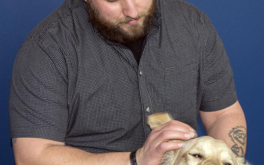 Retired Marine Cpl. Nick Gervasoni poses with his dog Penny in February 2015, at his place of employment in Alexandria, Va.: Veterans Curation Program.