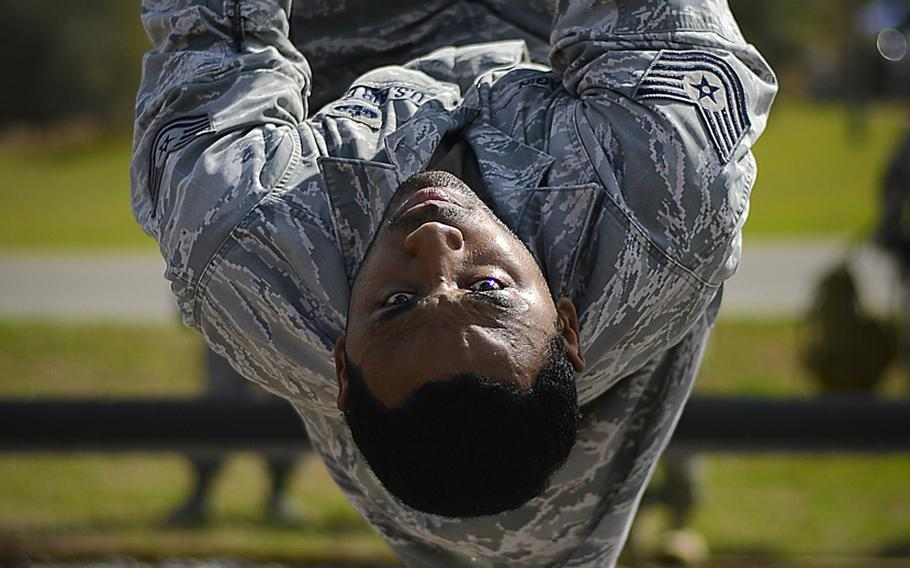 Tech. Sgt. Eric Dagin pulls himself across a rope obstacle on  March 3, 2015, at the Hillsborough County Sheriff?s Office firearms training center in Lithia, Fla.
