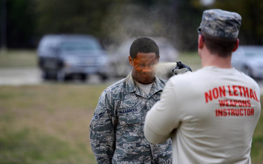 Airman 1st Class DeAaron Alexander receives a level-one contamination of oleoresin capsicum from Senior Airman Daniel Miller on Feb. 27, 2015, on Laughlin Air Force Base, Texas. After being hit with the pepper spray, the individual must then open their eyes, complete the five assessment stations and make it to the decontamination point on their own.