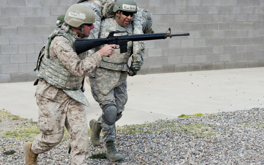 U.S. Army Sgt. 1st Class Matthew Girad is carried by U.S. Air Force Master Sgt. Eric Moss, while U.S. Marine Sgt. Trevor Andrews provides cover during small unit tactics training at Fort Bliss, Texas, on March 14, 2015, as part of Operational Contract Support Joint Exercise 2015.