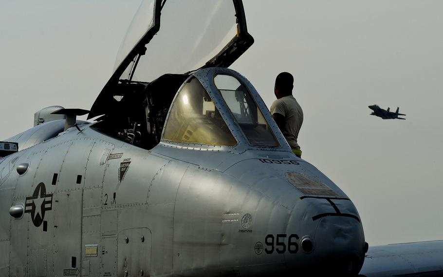 An A-10C Thunderbolt II sits on the flight line as an F-15E Strike Eagle flies over at RAF Lakenheath, England, on March 13, 2015. The A-10s and airmen are deployed out of Davis-Monthan Air Force Base, Ariz., as part of Operation Atlantic Resolve.