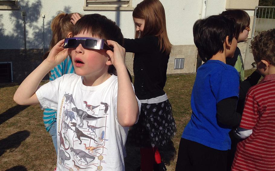 Tommy Morgenfeld, a second-grader at Boeblingen Elementary and Middle School in Stuttgart, Germany, watches a solar eclipse Friday, March 20, 2015, with protective glasses provided by his teacher, Karen Sipes.