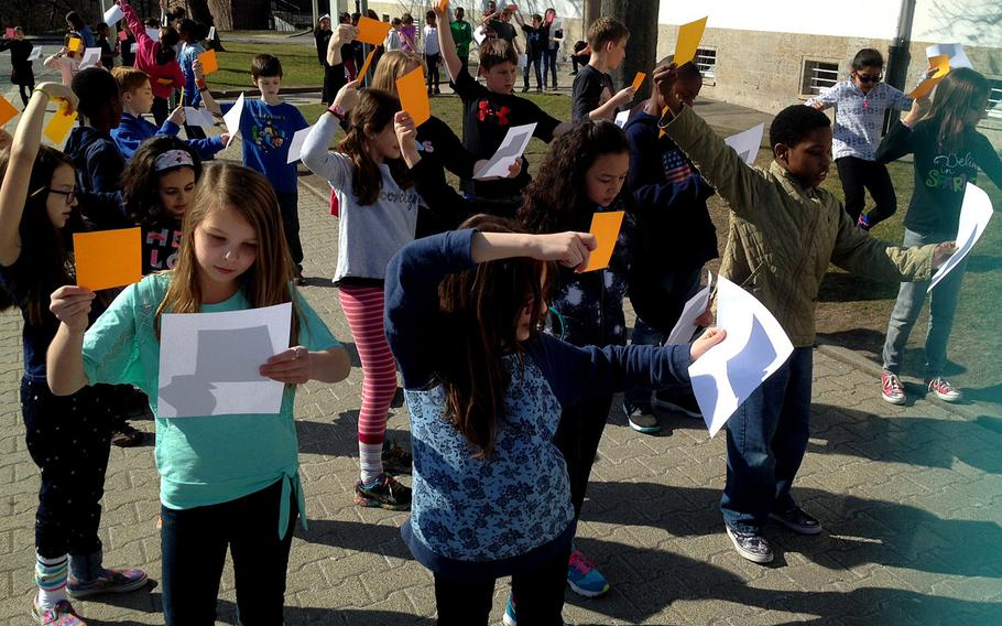 Fourth-graders at Boeblingen Elementary and Middle School in Stuttgart, Germany, position sheets of paper to capture the reflection of the sun being eclipsed by the moon on Friday morning, March 20, 2015. Students without protective glasses used alternative means to catch a glimpse of the eclipse.