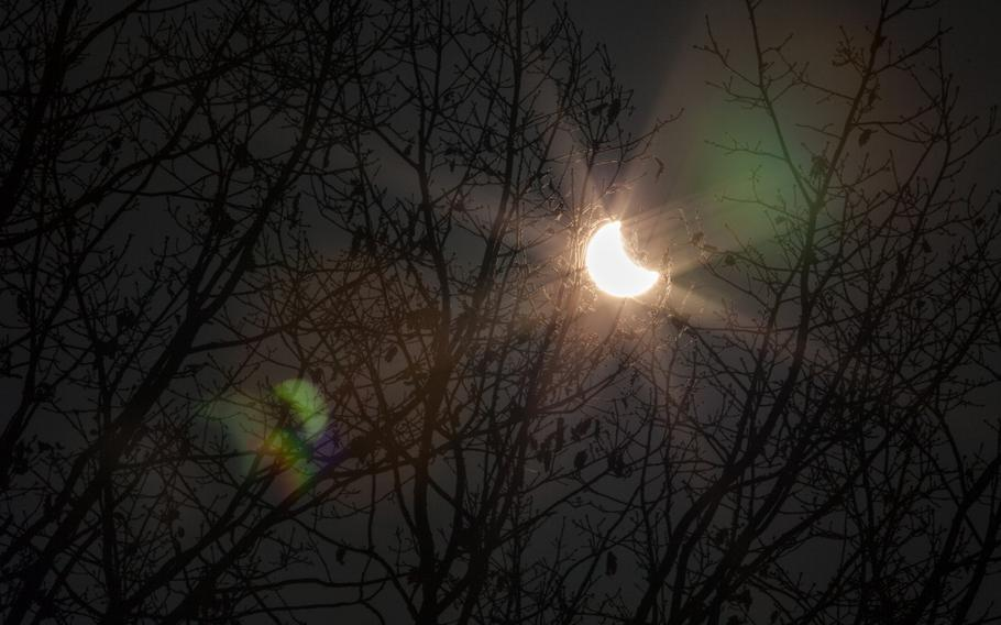 The partial eclipse of Friday, March 20, 2015, shines through a tree at the U.S. Army's Kleber Kaserne in Kaiserslautern, Germany.