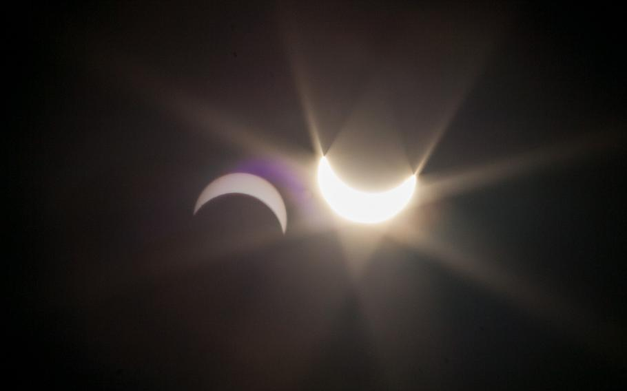 Internal reflections in a camera lens create an inverted image of the Friday, March 20, 2015, partial eclipse of the sun next to an image of the actual eclipse, right.