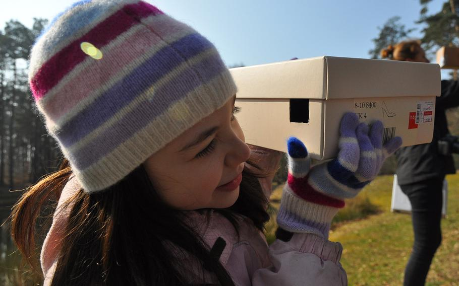 Ava Perez, 7, a second-grader at Ramstein Elementary School in Germany, peers through the small hole of a cardboard pinhole projector at the image of the partial solar eclipse Friday morning, March 20, 2015, on Ramstein Air Base.