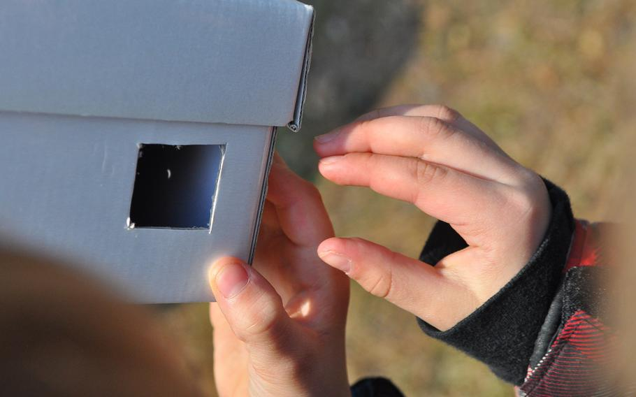 The sun's image appears as a tiny crescent moon inside the viewing hole of a cardboard pinhole projector. Yvonne Engels' second-grade class at Ramstein Elementary School spent the morning of March 20, 2015, exploring nature and viewing the partial solar eclipse over northern Europe through handmade pinhole projectors at the base pond on Ramstein Air Base, Germany.