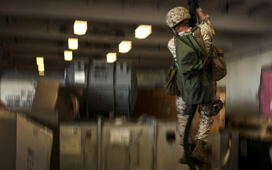 A U.S. Marine with Company L, Battalion Landing Team 3rd Battalion, 1st Marine Regiment, 15th Marine Expeditionary Unit, fast ropes in the hangar bay of the USS Essex during Composite Training Unit Exercise off the coast of San Diego on March 23, 2015.