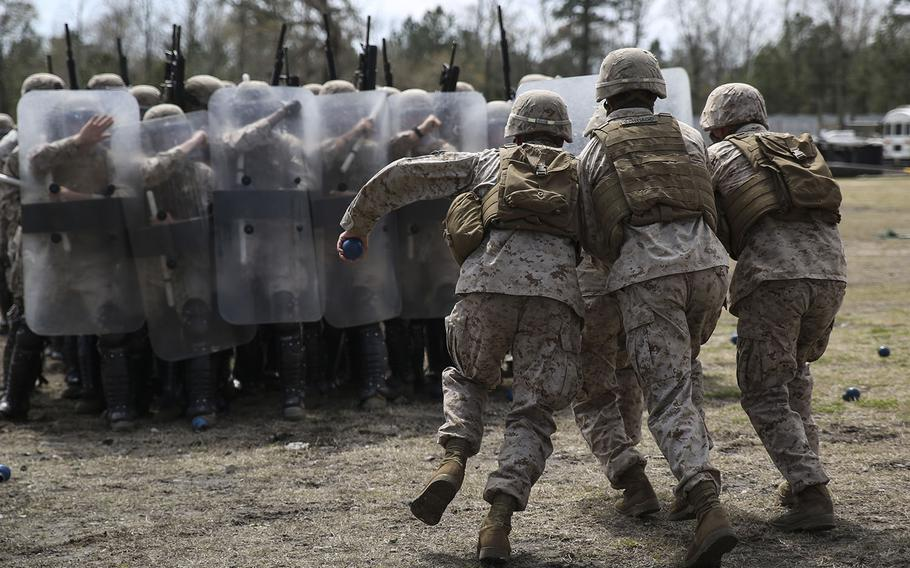 Marines with the 2nd Battalion, 6th Marines, acting as role-players, rush into a blockade of Marines as part of a riot-control exercise aboard Camp Lejeune, N.C., on March 24, 2015.