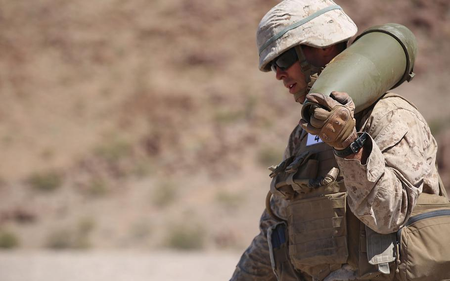 Cpl. Joshua J. Syverson, combat engineer, Engineer Platoon, Headquarters and Service Company, Ground Combat Element Integrated Task Force, carries a 155 mm shell during cache reduction as part of a Marine Corps Operational Test and Evaluation Activity assessment at Range 114, Marine Corps Air Ground Combat Center Twentynine Palms, California, on March 23, 2015.