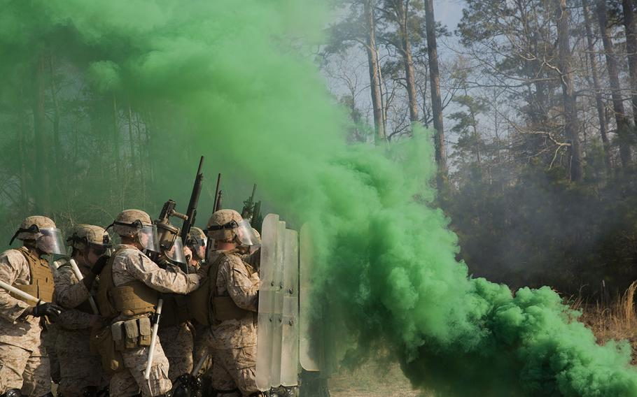 Smoke grenades thrown by course instructors envelop Marines with 2nd Battalion, 6th Marine Regiment, in thick, green smoke during a nonlethal weapons training exercise aboard Camp Lejeune, N.C., on March 25, 2015.