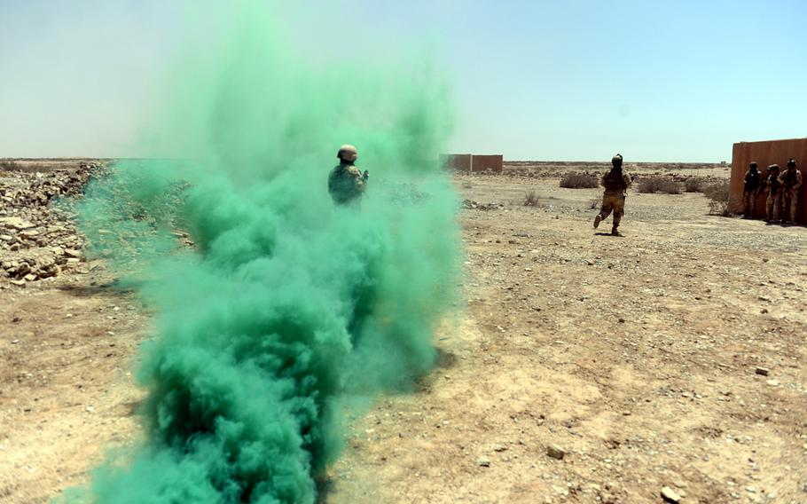 Iraqi troops run through a smoke grenade to assault a building during an exercise at a Besmaya, a training camp south of Baghdad, on April 26, 2015.