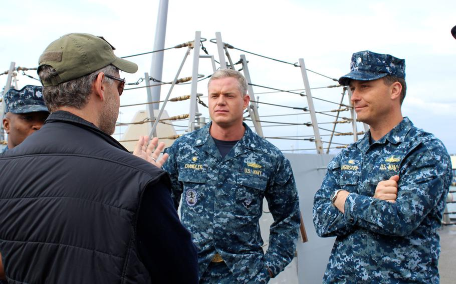 """Eric Dane, center, who plays Cmdr. Tom Chandler on the TNT Drama """"The Last Ship,"""" and Cmdr. Chanden Langhofer, right, the real-life commanding officer of the USS William P. Lawrence, chat with Steven Kane, co-creator and executive producer of the show, during filming on the ship at Naval Base San Diego."""