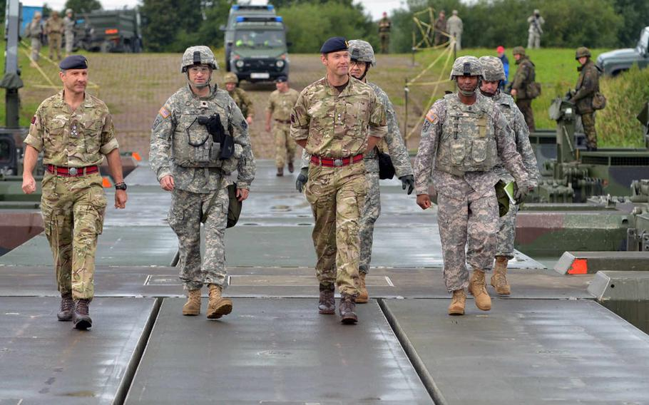 From left, British army Brigadier Robert Walton-Knight, commander of 8th Engineer Brigade; U.S. Army Lt. Col. Doug Lynch, commander of 5th Battalion; 7th Air Defense Artillery Regiment; British army Lt. Col. Alan Mason, commander of the 75 Engineer Regiment; and Sgt. Maj. George Clark of 5-7 ADA, cross an M3 Amphibious Rig bridge over the Wesel River in Germany. Patriot launcher stations later crossed the bridge during Minden Shock, a multinational training exercise, Tuesday, July 28, 2015.