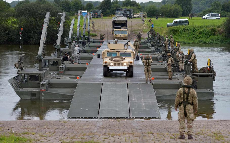 A convoy of U.S. Army vehicles cross the Weser River over a M3 Amphibious Rig bridge built by British and German army engineers during a training exercise in Germany dubbed Minden Shock. Soldiers of the 10th Army Air and Missile Defense Command's 5th Battalion, 7th Air Defense Artillery Regiment, drove a Patriot missile battery over the bridge before setting up the battery nearby, Tuesday, July 28, 2015.