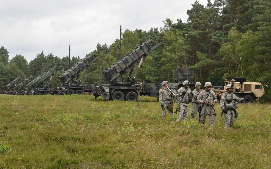 Patriot missile launchers of Battery D, 5th Battalion, 7th Air Defense Artillery, stand ready in a field near Minden, Germany, less than two hours after they crossed the Weser River over a temporary bridge during Minden Shock, a training exercise that included American, German and British soldiers, with observers from Belgium and Poland.