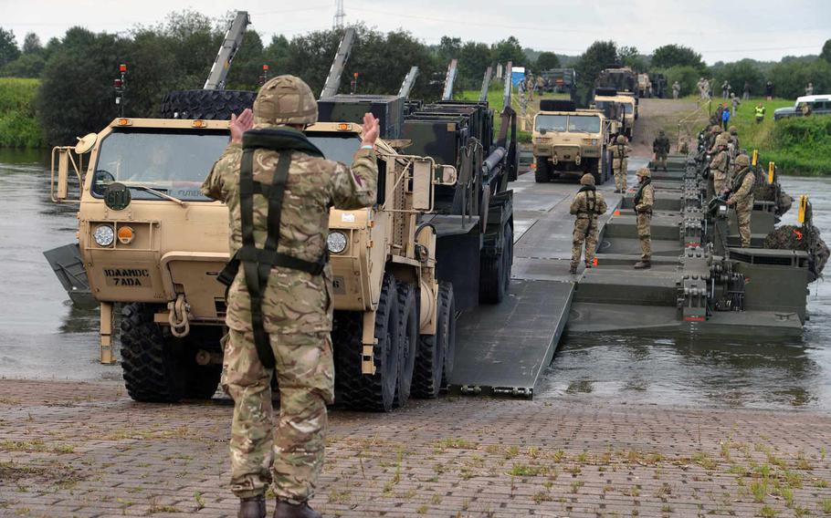 A British soldier guides a Patriot launcher station of 5th Battalion, 7th Air Defense Artillery Regiment, over an M3 Amphibious Rig bridge spanning the Weser River, Tuesday, July 28, 2015, during Minden Shock, a multinational training exercise.