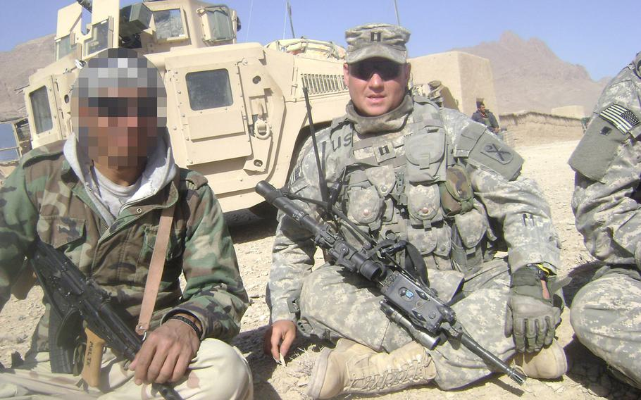 """Longtime U.S. military interpreter """"Malik,"""" left, on a patrol with American forces in Farah province, Afghanistan, in 2008. Despite working for more than a decade with U.S. troops and facing death threats from the Taliban, Malik has been waiting five years for a visa created specifically for former Afghan and Iraqi interpreters facing danger."""