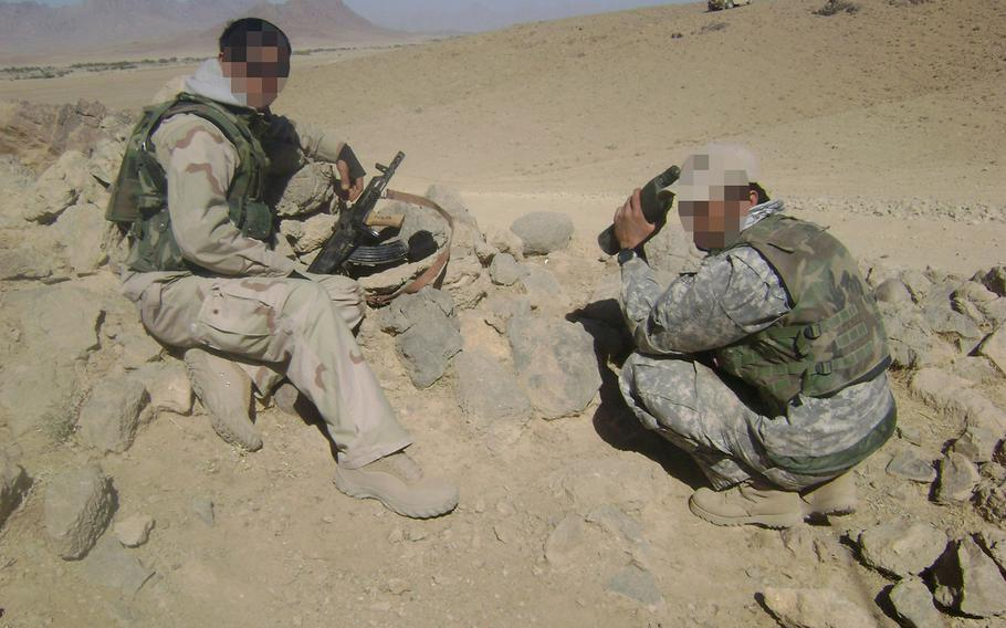 """""""Malik"""" and a fellow interpreter on patrol in Herat province in 2007. Thousands of Afghan interpreters who worked for U.S. forces are stuck in limbo while awaiting a Special Immigrant Visa, created to give safe passage to the U.S. for those facing threats for their service to America."""