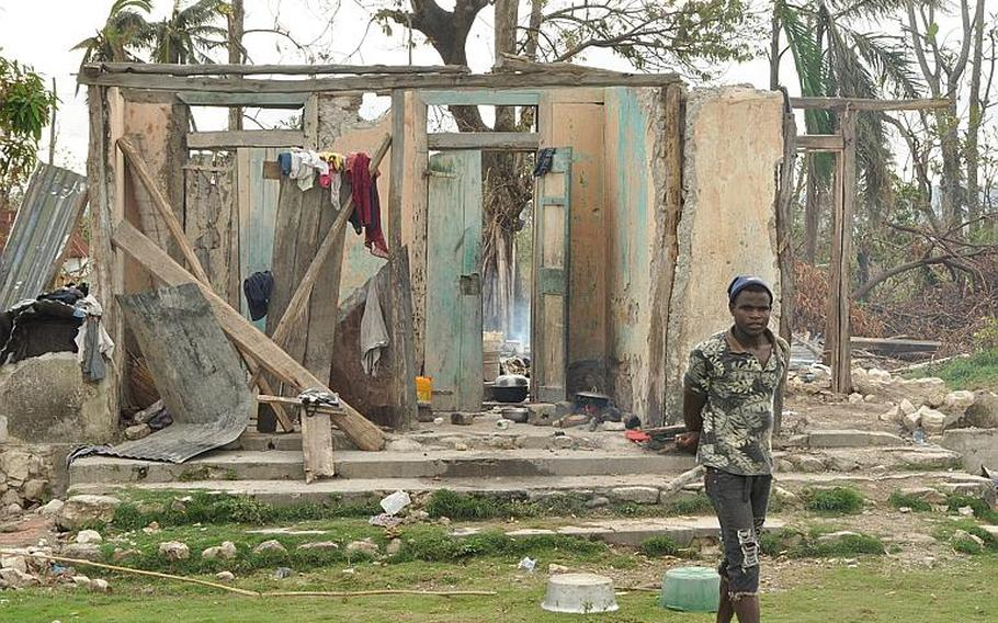 A man stands outside a destroyed home in southwest Haiti on Oct. 17, along the road between the southern coastal city of Les Cayes and the village of Jabouin in the nearby mountains. Hurricane Matthew smacked into the region two weeks ago, leaving an estimated 90 percent of the homes damaged or destroyed.