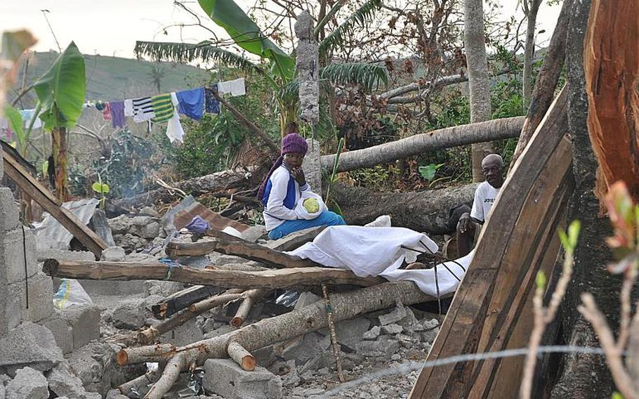 A woman holding a baby sits atop rubble in southwestern Haiti on Oct. 17, along the road between the southern coastal town of Les Cayes and the village of Jabouin in the nearby mountains. Hurricane Matthew smacked into the region two weeks ago, leaving an estimated 90 percent of the homes damaged or destroyed.