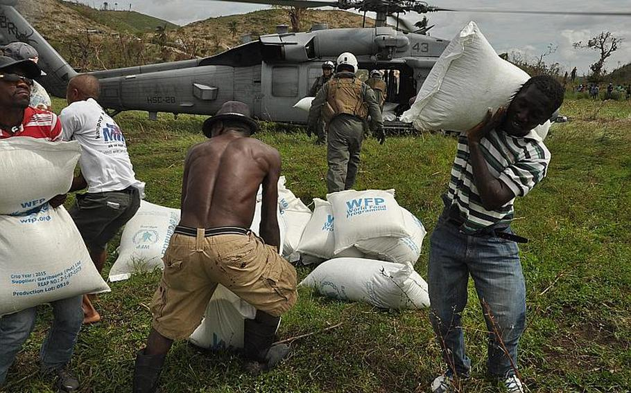Villagers work with Navy pilots and Marines to offload relief supplies from a Navy helicopter delivered to the village of Jabouin in southwest Haiti on Oct. 18. The village was badly hit by Hurricane Matthew two weeks ago, which destroyed homes and crops, leaving many people unsheltered and without food or livelihood.