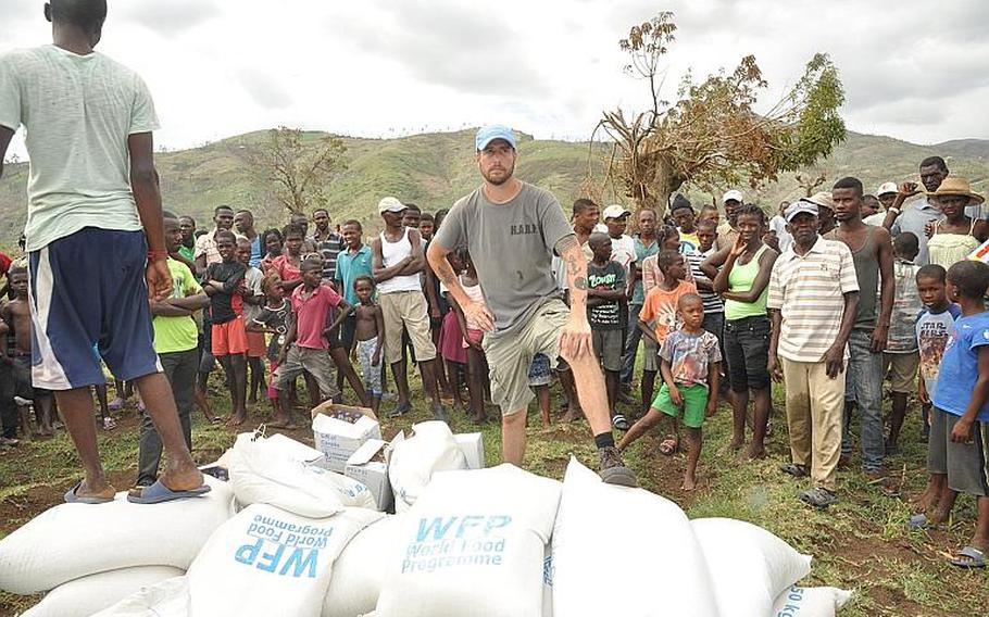 William Gagan, of the Humanitarian Aid and Rescue Project, guards a delivery of relief supplies to the southwest Haiti village of Jabouin on Oct. 18, with the help of one of the villagers. Gagan's organization arranged for the aid drop, and is working with other volunteers to provide basic medical help to villagers after Jabouin was struck by Hurricane Matthew.