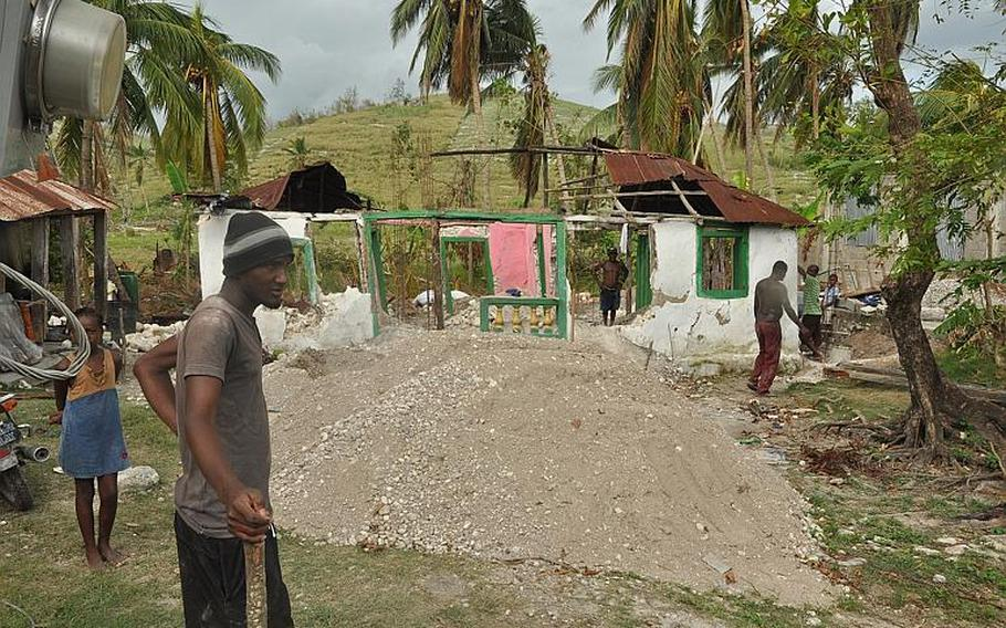 A man stands outside a destroyed home in southwest Haiti on Oct. 17, along the road between the southern coastal city of Les Cayes and the village of Jabouin in the nearby mountains. Hurricane Matthew smacked into the region two weeks ago, leaving an estimated 90 percent of the homes damaged or destroyed. damaged or destroyed.