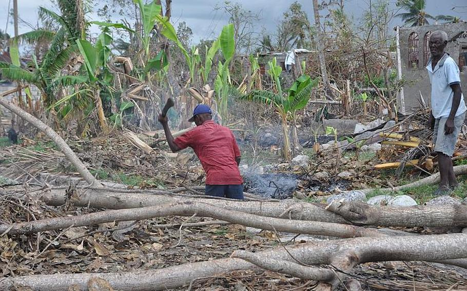 A man chops through a thicket of fallen trees in southwest Haiti on Oct. 17, along the road between the southern coastal city of Les Cayes and the village of Jabouin in the nearby mountains. Hurricane Matthew smacked into the region two weeks ago, leaving an estimated 90 percent of the homes damaged or destroyed.