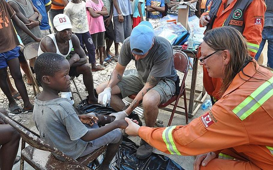 A little boy in the hurricane-struck village of Jabouin in southwest Haiti holds tight on Oct. 18 as American volunteer William Gagan, center, cleans a wound on the boy's leg. Sylvie Montier, a Canadian volunteer holds his hand.