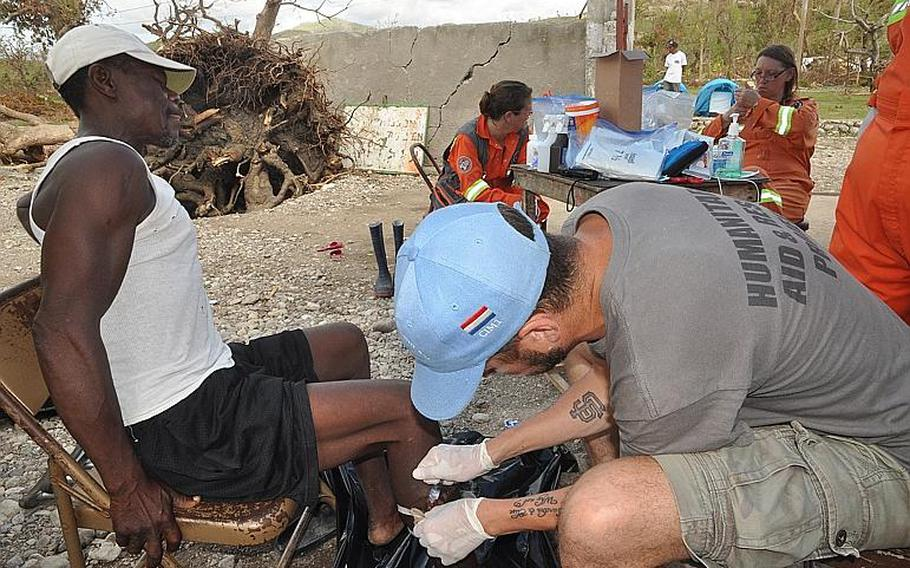 William Gagan, of the Humanitarian Aid and Rescue Project, right, tends to a deep leg wound on Jackson Bogait, a villager in the southwest Haiti village of Jabouin on Oct. 18. Bogait was wounded during Hurricane Matthew, when a piece of corrugated sheet metal off a roof flew at him during the Oct. 4 storm.