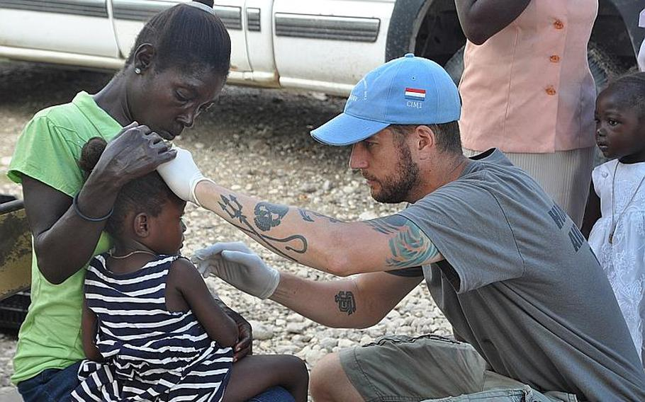 William Gagan, of the Humanitarian Aid and Rescue Project, right, tends to sick child in the southwest Haiti village of Jabouin on Oct. 18.