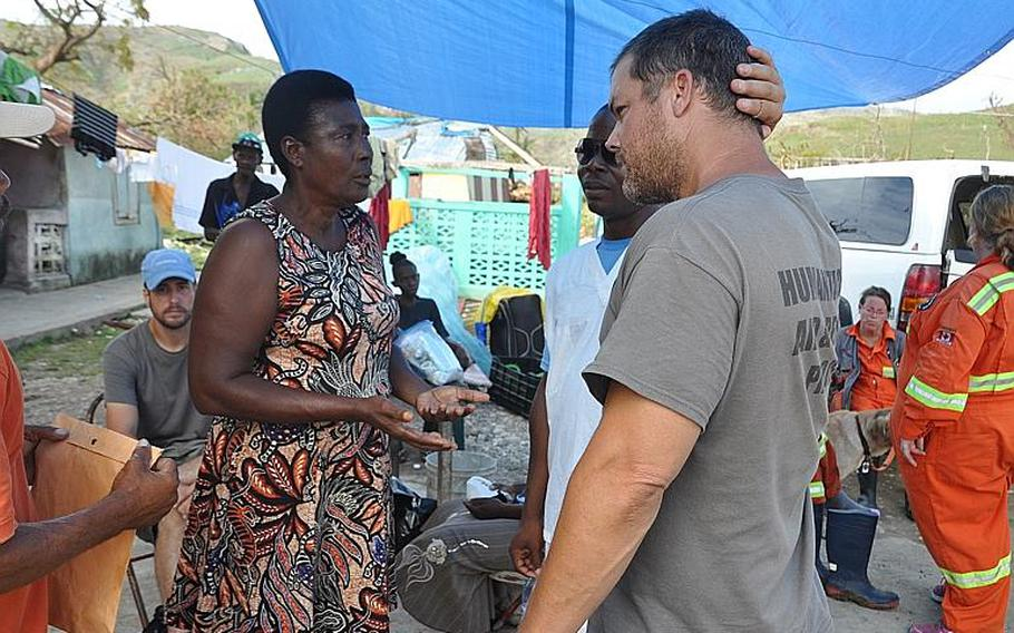 Yvette Moise, left, a resident of Lansing Michigan and native of the southwest Haiti village of Jabouin, talks with Navy veteran Burke Bryant, right, co-founder of Humanitarian Aid and Rescue Project on Oct. 18. Burke's group is helping Moise, who has a house and land in the village, organize food and medical help for members of the village after it took a direct hit from Hurricane Matthew.