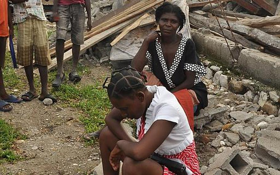 A family sits atop the rubble of their home in the village of Jabouin in southwestern Haiti on Oct. 18, after taking a direct hit from Hurricane Matthew two weeks ago. The woman uses the megaphone to walk around the village in the morning urging her neighbors to put their faith in Jesus.